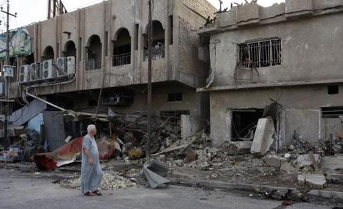 A man walks past the site of Wednesday's car bomb attack in Baghdad